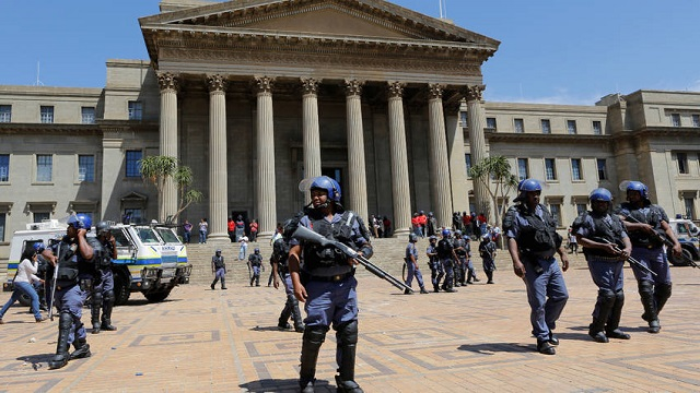 South African police forces members patrol the Wits University campus during ongoing clashes with #