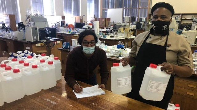 Ronn Mager and Siyasanga Nkuna from Residential Operations at Rhodes University collect hand sanitiser from the Pharmacy Faculty to start preparations for the next group of returning students