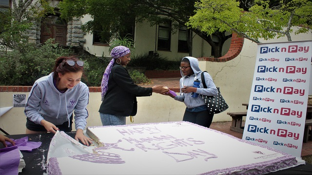 Project Manager and Treasurer General handing out cake at The Kaif for Human Rights Day